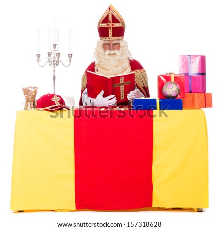 Sinterklaas is working at his desk, at a white background