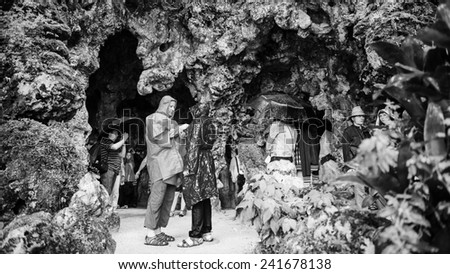 SINTRA, PORTUGAL - JUN 22, 2014: Unidentified tourists hide in one of the caves of the Quinta da Regaleira estate, Sintra,Portugal. Quinta da Regaleira is a UNESCO World heritage site