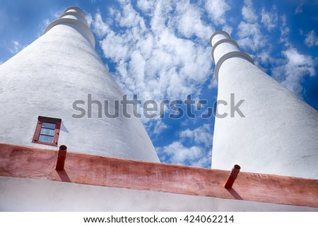 SINTRA, PORTUGAL - MAY 1, 2015: The two tall, white kitchen chimneys of the royal palace in Sintra, Portugal are distinctive architectural features of this historic landmark. - stock photo