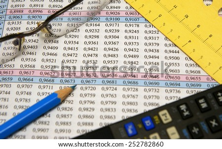 Sinus and cosines mathematical table together with glasses, blue pencil, measurement and calculator - stock photo