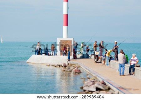 Siofok, Hungary - September 2014. Many man fishing on a pier in Siofok, a city on the Lake Balaton. - stock photo