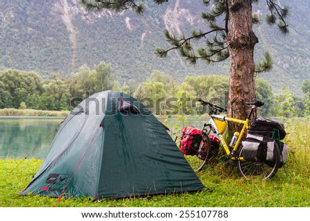 SION, SWITZERLAND - AUGUST 12: Lonely campsite by the lake on a rainy morning in Switzerland Alps near Sion on August 12, 2014. Cycling and camping is a popular way of visiting a country. - stock photo