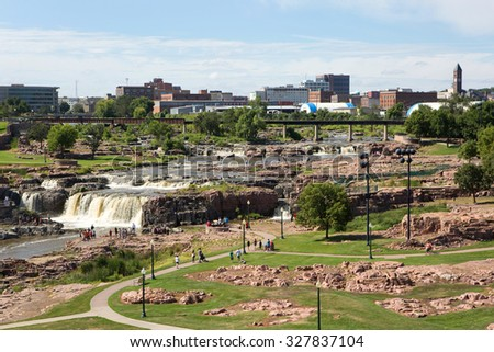 SIOUX FALLS, SOUTH DAKOTA, USA - AUGUST 8, 2015: Tourists visit Falls Park in Sioux Falls, South Dakota, USA with city skyline in the background on August 8, 2015. - stock photo