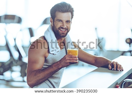 Sip of freshness after great workout. Side view of handsome young men in sportswear holding glass of fresh orange juice and looking at camera with smile while sitting at bar counter at gym - stock photo
