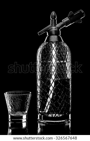 siphon with soda copulation on the table on a black background with an empty Cup - stock photo