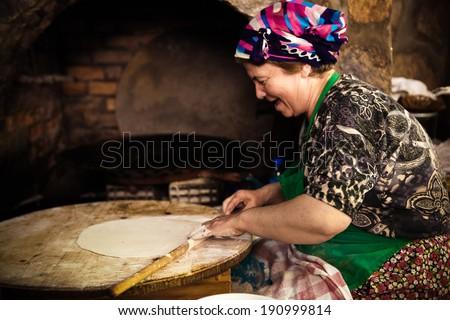 SIRINCE, TURKEY - MAY 24: Woman cooks a traditional Turkish pancake on May 24, 2011 in Sirince, Turkey - stock photo