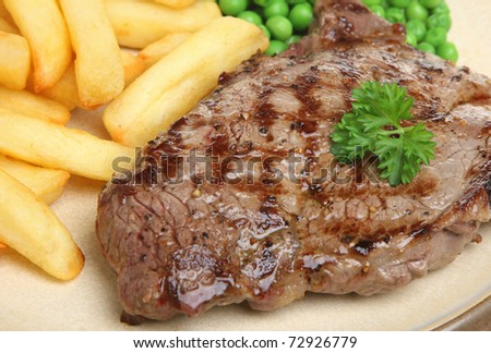 Sirloin beef steak with chips and peas.