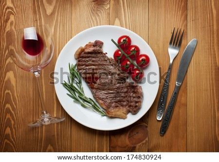 Sirloin steak with rosemary and cherry tomatoes on a plate with wine. View from above - stock photo