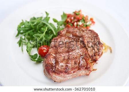 Sirloin steak with tomato tartare on white plate studio shot - stock photo