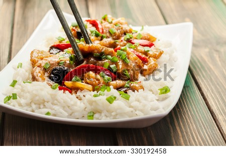 Sirloins on sweet and sour sauce served with boiled rice - stock photo