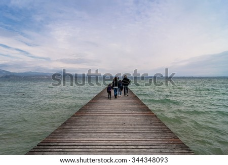 SIRMIONE, ITALY - APRIL 4, 2015: tourists on pier with cloudy sky in Sirmione, Italy. Sirmione is one of lake Garda most popular cities visited by tourists every summer.