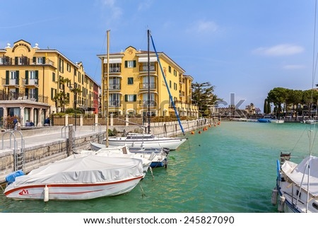 SIRMIONE, ITALY - APRIL 01, 2012: Yachts and boats at small marina and luxury hotels on background in Sirmione - famous popular tourist resort and small medieval town on Lake Garda. - stock photo