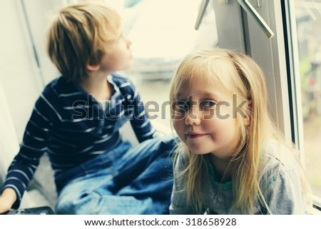 Sister and brother are sitting near the window - stock photo