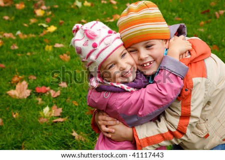 sister and brother embrace in autumnal park