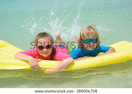 Sister and brother have fun with air mattress at the beach  - stock photo