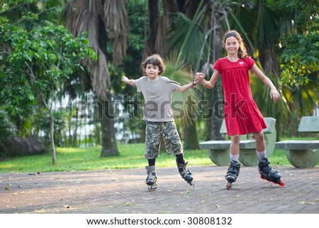 Sister and brother having fun rollerblading in an outdoor park - stock photo