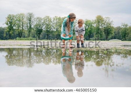 Sister and brother looking in puddle. Little girl and boy splash
