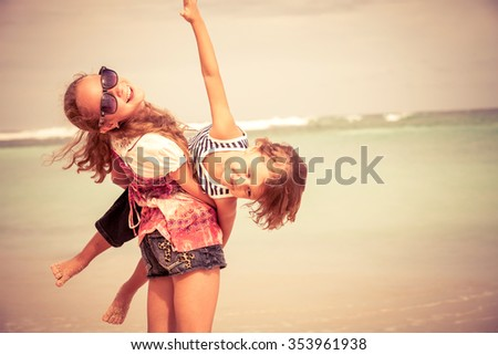 Sister and brother playing on the beach at the day time. Concept Brother And Sister Together Forever - stock photo