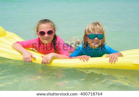 Sister and brother playing with air mattress at the beach  - stock photo