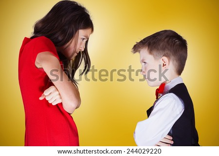Sister and brother siting in front of each other with mad,mean,rivalry emotions over yellow background.Concept conflict,family - stock photo
