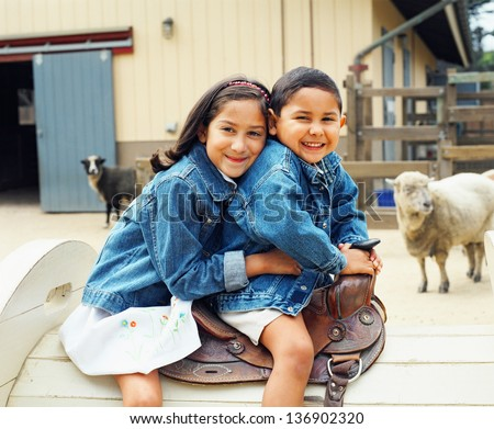 Sister and brother sitting on saddle - stock photo