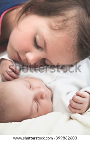 Sister and her newborn brother sleeping