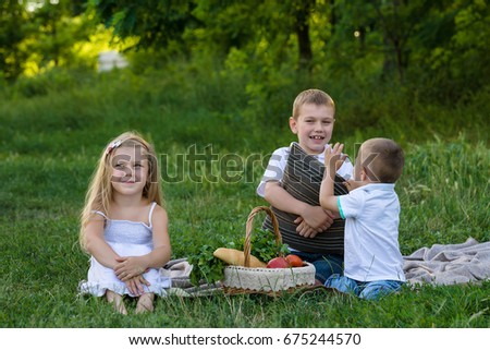 Sister and two brothers in the summer garden with picnic basket