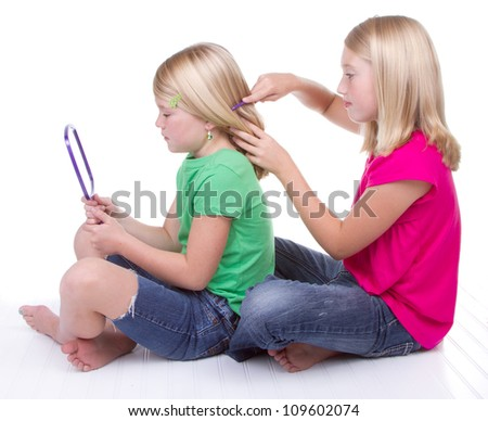 sister combing younger sisters hair, white background - stock photo