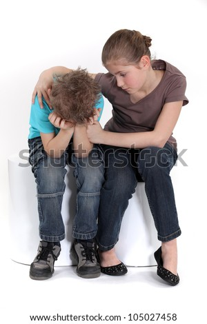 Sister comforting her little brother. - stock photo