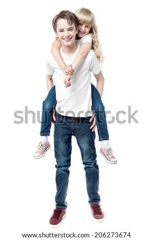 Sister enjoying piggyback ride with brother - stock photo