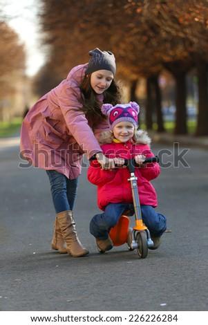 sister girls walking on the street  - stock photo