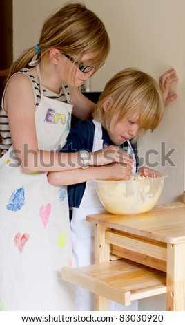 Sister helping her brother to make a cake