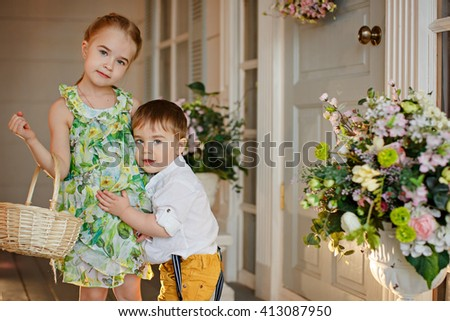 Sister in a green dress and her younger brother, are embracing in the background interior of the house and flowers - stock photo