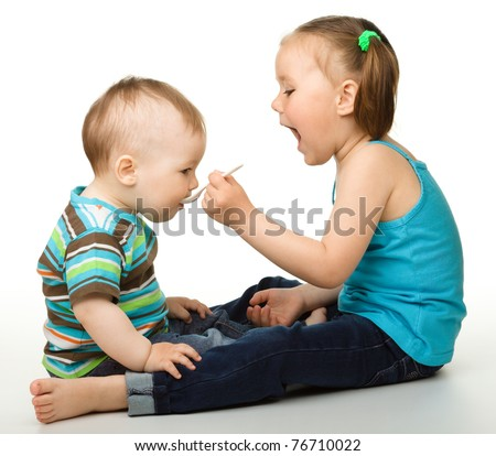Sister is feeding her little brother using spoon, isolated over white - stock photo