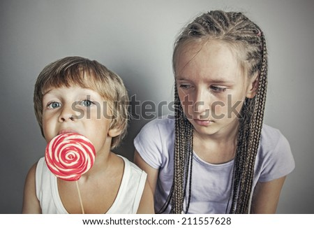 sister jealous brother who eats candy - stock photo