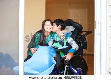 Sister kissing and hugging disabled little nine year old  brother in wheelchair indoors - stock photo