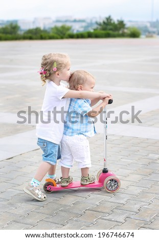 sister teaches toddler brother to ride a scooter - stock photo