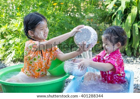 Sister (two cute asian girl) play water  in her little plastic basin on Songkran festival (New year) in Thailand. - stock photo