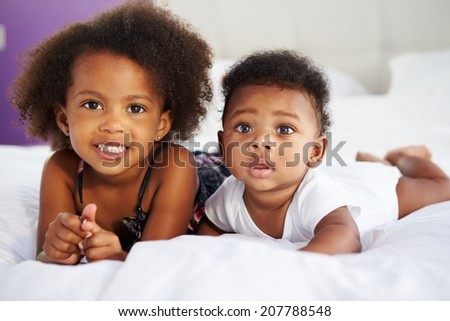 Sister With Baby Brother Lying On Parent's Bed - stock photo