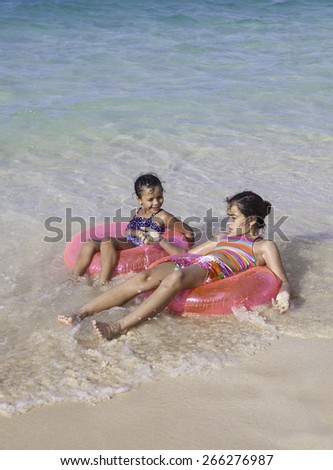 sisters at the beach with float rings