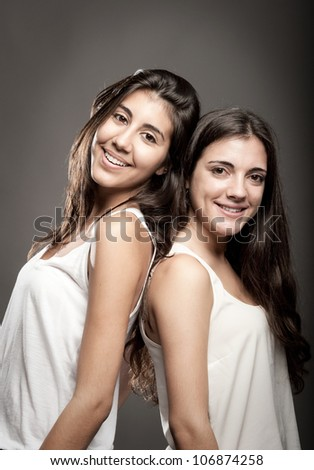sisters back to back - stock photo