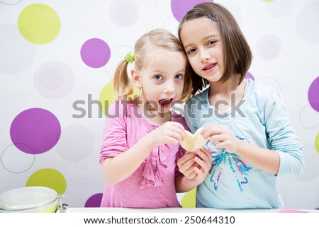 Sisters baking, heart cake, happy child - stock photo
