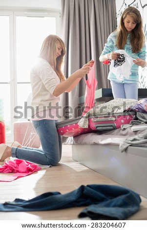 Sisters cleaning bedroom