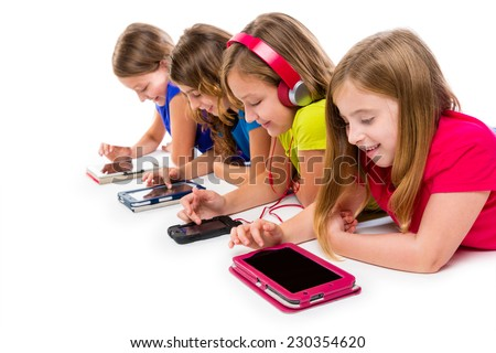 sisters cousins kid girls with tech tablets and smartphones in a row lying on white background - stock photo