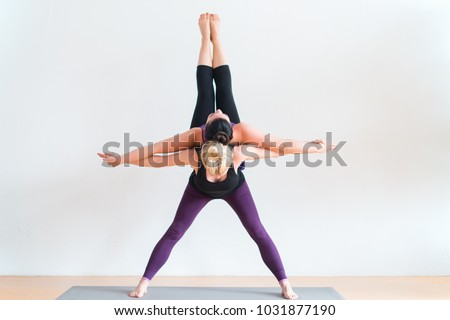 Sisters Doing A Duo Yoga Pose
