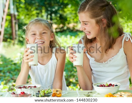 Sisters eating in the garden. Drink sour-milk - stock photo