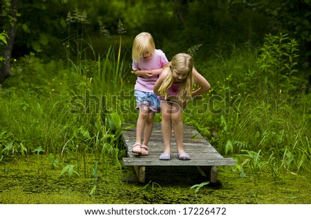 Sisters exploring a small pond in the north woods of Minnesota - stock photo