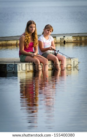 Sisters fishing together - stock photo