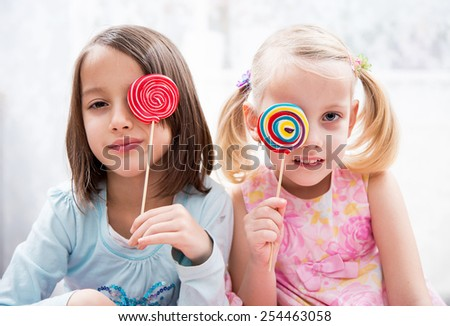 sisters have fun, colored lollipops - stock photo