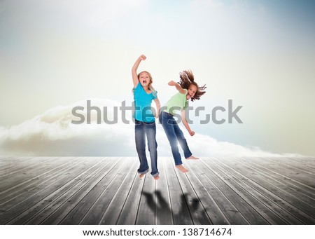 Sisters having fun jumping over wooden boards leading out to the horizon - stock photo